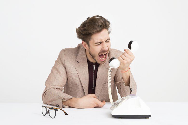 クレームの電話を入れる男性