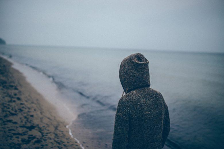 人生に疲れて海辺を歩く男性