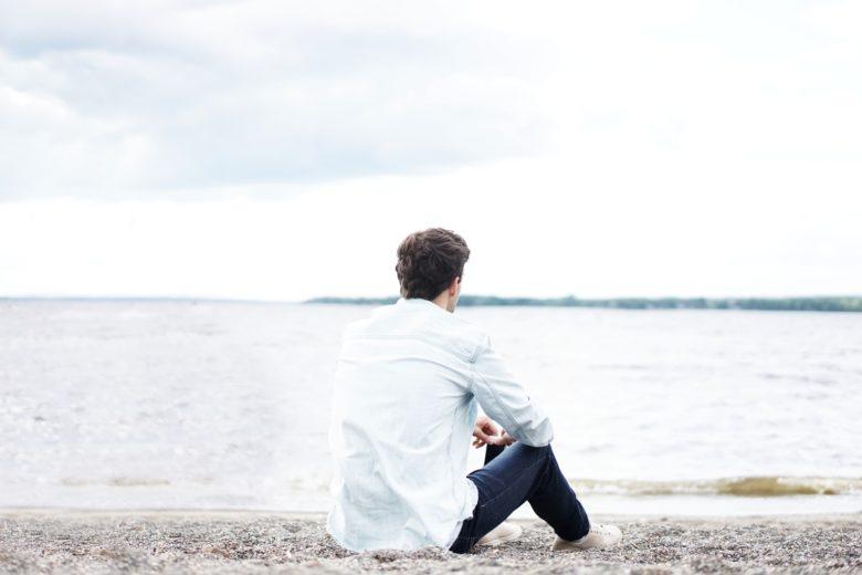 海を見つめて考え込む男性